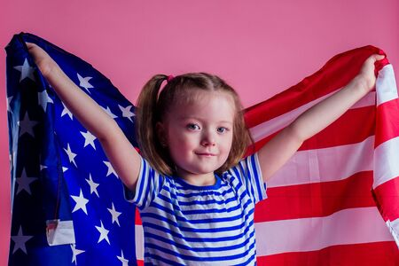 caucasian happy female baby in striped blue and white navy suit holding american flag in hand on a pink background in the studio.English language learning and freedom future profession army navy dream