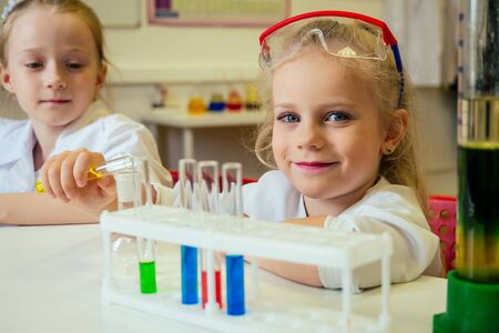 two blonde chemist school kid student little girls girlfriend sisters chemical experiment white medical gown classroom science