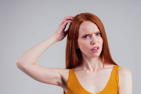 attractive redhead young woman with perfect skin wearing yellow shirt, looking at camera holding arm on her chin and think white studio background.hair loss concept