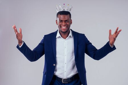 Happy successful young african american businessman portrait wearing a crown holding a laptop lottery winner