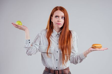 redheared hungry business woman in striped shirt eating USA burger visa traveler white background studio choosing healthy food apple