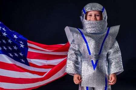 adorable female child in costume helmet playing bright foil silver cosmonaut in uniform with american flag black background in the studio.patriotism July 20, 1969 landing on the moon concept space day