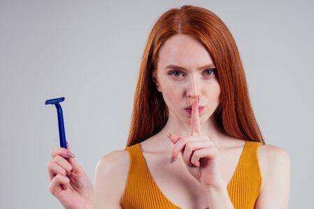 Beautiful young woman with razor and epilator on white studio background