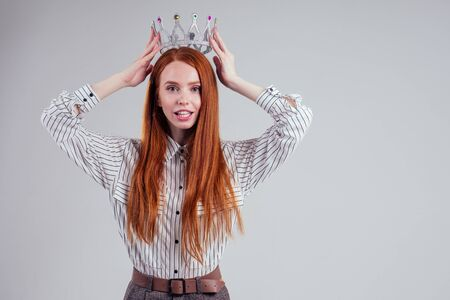 Pretty redhead businessman with crown n a striped shirt white background studio Stock Photo