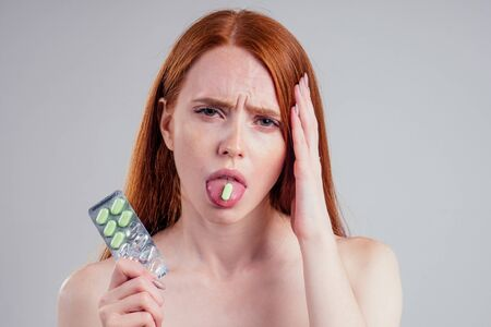attractive ginger hair female dose capsule head headache and toothache pain with one pack of pills thinking white background studio.