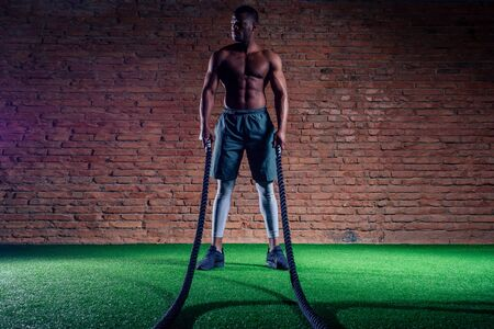 multiethnic bare sexy chest sportsmen exercising with battle ropes at the gym