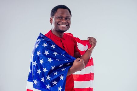 african american man looking at camera and proudly holding american flag at studio