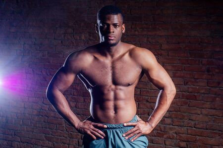 young muscular african american man doing push-ups and looking away
