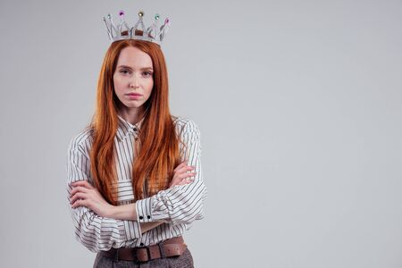 Pretty redhead businessman with crown n a striped shirt white background studio