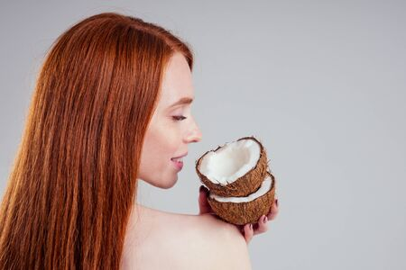 young ginger redhead woman with ideal skin and perfect redhaired hear holding coco nut in hands in white studio backgroung. Stock Photo