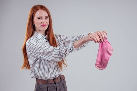 Female redhead in a striped shirt gesture smells bad holding a dirty pink sock out a disgusted look on her face in studio white background Stock Photo