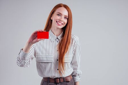 attractive redhead caucasian businesswoman wearing striped shirt holding credit card studio white background black friday sale cashback