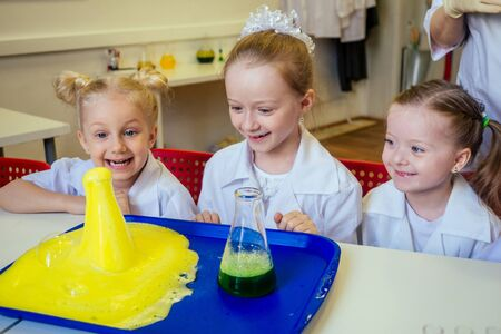 group of school girl kids with teacher in school laboratory making experiment observing the chemical reaction with the dye with vinegar and soda volcano wearing white gown uniform glass