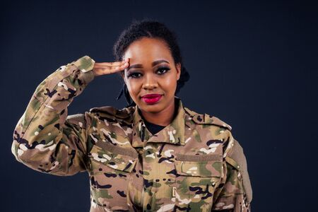 afro american army latin soldier in camouflage clothes hair dreadlocks evening makeup and big lips on a black background in the studio.