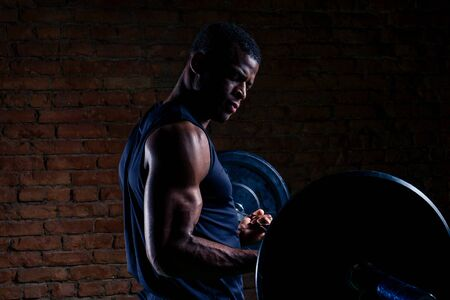 african american man with dumbbell weight training equipment gym