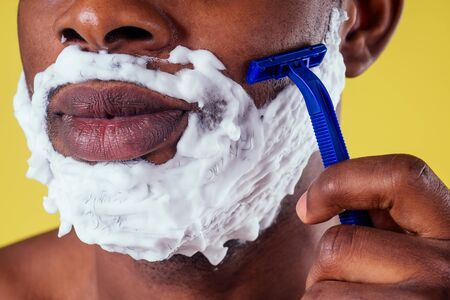 African-american man with razor and shaving foam on his face.