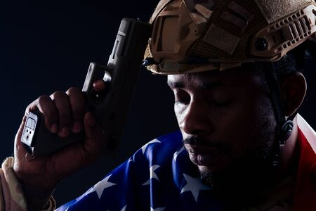 american man in camouflage suit aiming with a pistol studio shot