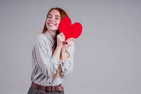 Happy redhead girl businesswoman in a striped shirt model sending air kiss with decorative hearts Valentines Day gift on white background studio