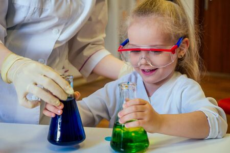 surprised and amazed clever blonde school girl chemist in eyeglasses and white medical gown making science experiments chemistry ,mixing different chemical solutions in laboratory classroom.
