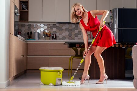 beautiful girl floor dancing with mop and bucket in evening dress and heel shoes in a cozy apartment with a TV in the hall.wife is waiting for her husband at home.funny mother cleaning company
