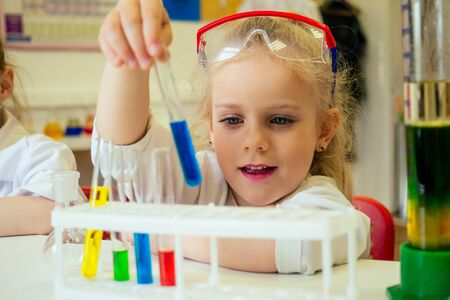 surprised and amazed clever blonde school girl chemist in eyeglasses and white medical gown making science experiments chemistry ,mixing different chemical solutions in laboratory classroom Zdjęcie Seryjne