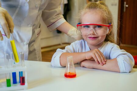 clever blonde school girl chemist in eyeglasses and white medical gown making science experiments chemistry ,mixing different chemical solutions in laboratory classroom