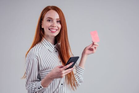 red-haired businesswoman in a striped shirt happy using mobil phone and holding a red plastic card cardboard on white background studio black friday sale cashback