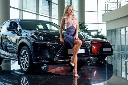 business woman in dress and high heel footwear posing near a luxury car in showroom