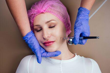 Mujer recibiendo masaje facial con spray de aire oxigenado .Terapia de oxígeno en el salón spa.Cerrar la mejilla del paciente.