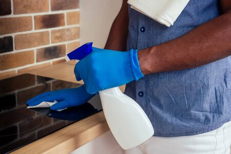 african man cleaning cooktop cooker hood at home ,Brick wall background.