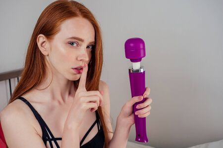 sensuality redhaired ginger female model body in black lacy, underwear lingerie panties and bra holding finger in mouth with purple toys in hands bedroom