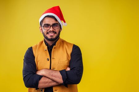 indian man wearing stylish traditional kurta great smile in santa hat with gift box on yellow background studio.dark-skinned Santa Claus congratulating merry christmas Banco de Imagens