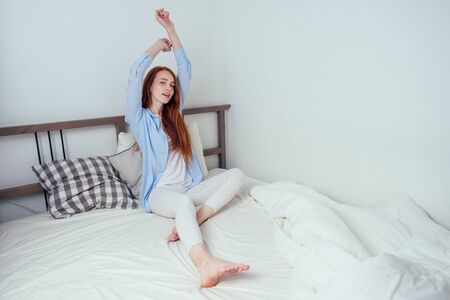 happy caucasian beautiful redhaired ginger freckles female awake in bedroom Banco de Imagens