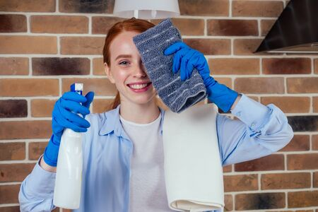 caucasian beautiful red-headed female in casual clothes wearing rubber glove and holding chemica spray in kitchen