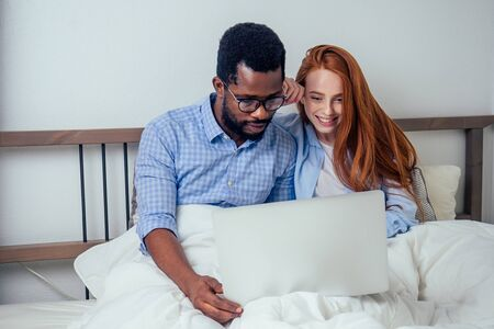 ginger redhaired european female and handsome afro african male together hugging lying in bedroom at home cozy apartment and watching news on laptop.lifestyle interracial family