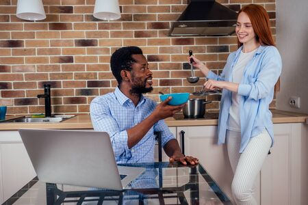 caucasian redhaired ginger woman cooking traditional russian soup borscht to her african-american man in kitchen Stock fotó