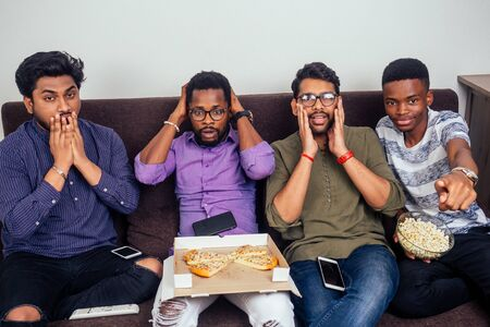 african american friends watching horror movie and eating pizza at home, copy space Imagens