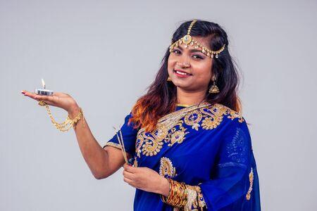 beautiful indian female tradition dress blue saree prayers candle happy diwali light studio white background