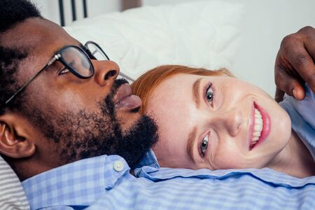redhaired ginger caucasian happy female and multi-ethnic afro man together lying in bed bedroom.lifestyle tolerance concept.