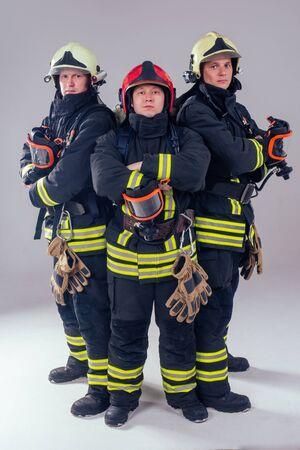 portrait three strong fireman men in fireproof uniform white background studio