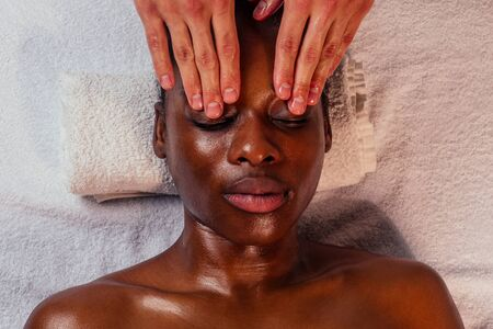 beautiful african american female getting Ayurveda face massage by the white-skinned hands of man in spa salon.
