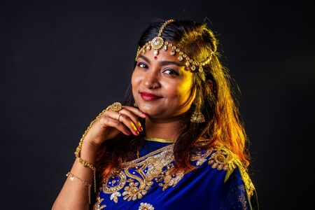 indian beautiful fashion brunette woman in blue traditional wedding rich sari with make-up on black studio background Archivio Fotografico - 132192239