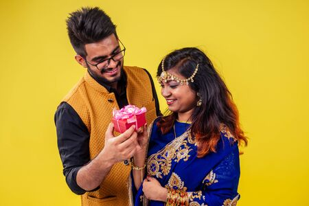 beautiful indian woman in traditional sari and happy hindu male getting together gift box in yellow studio background. Happy divali day