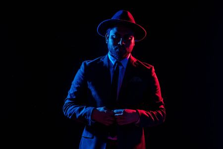Young handsome model posing in a studio in a trendy neon light in a stylish suit and hat