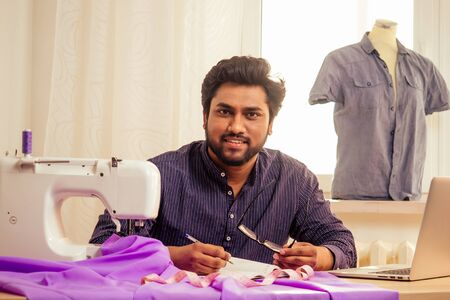 tailor asian man designer sewing clothes on sewing machine next to laptop studio workplace 스톡 콘텐츠