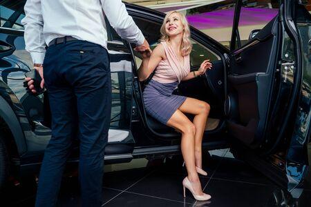 Caballero chofer ayudando a la joven mujer de negocios en vestido y calzado de tacón después de la fiesta nocturna en el club, para salir de un coche de lujo Foto de archivo