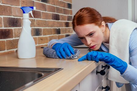 caucasian beautiful red-headed female in casual clothes wearing rubber glove and holding chemica spray in kitchen Archivio Fotografico