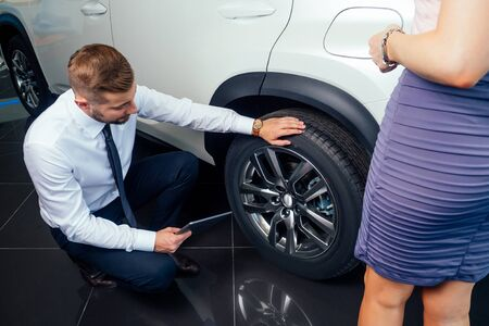 saleman mechanic showing the tread of a tire to a female customer in showroom Standard-Bild