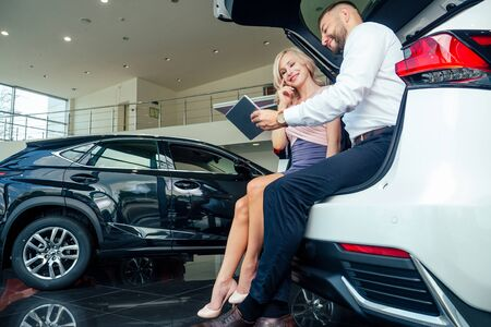caucasian salesman in suit showing catalog to beautiful female blonde well-dressed customer in dealership salon