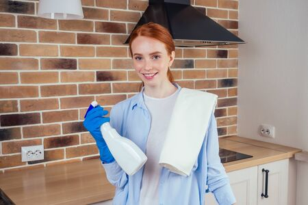 caucasian smiling redhaired woman working in kitchen in casual clothes and rubber gloves